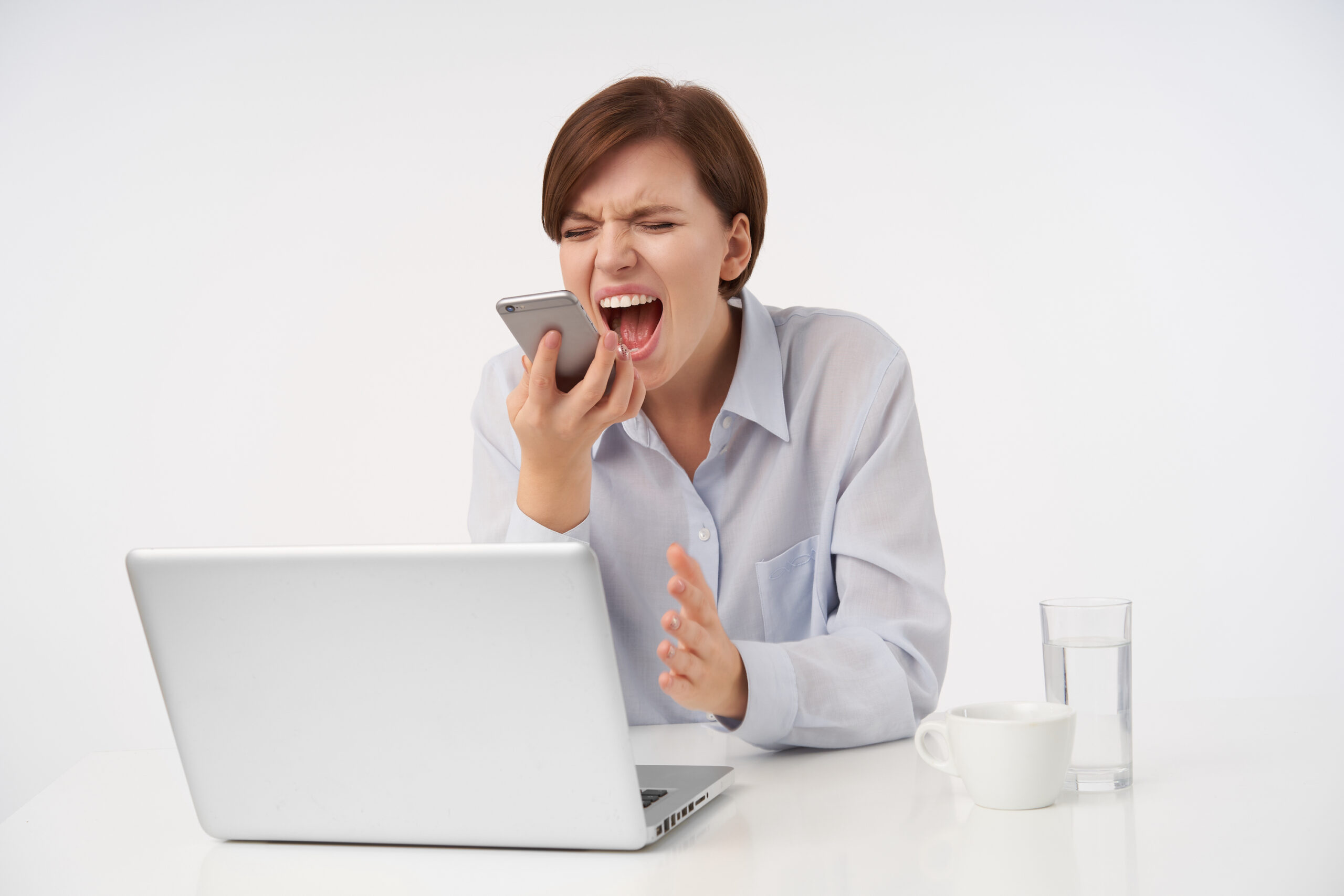 Stressed young short haired brunette woman frowning her face with closed eyes while shouting angrily into handset, having bad day at work, isolated over white background