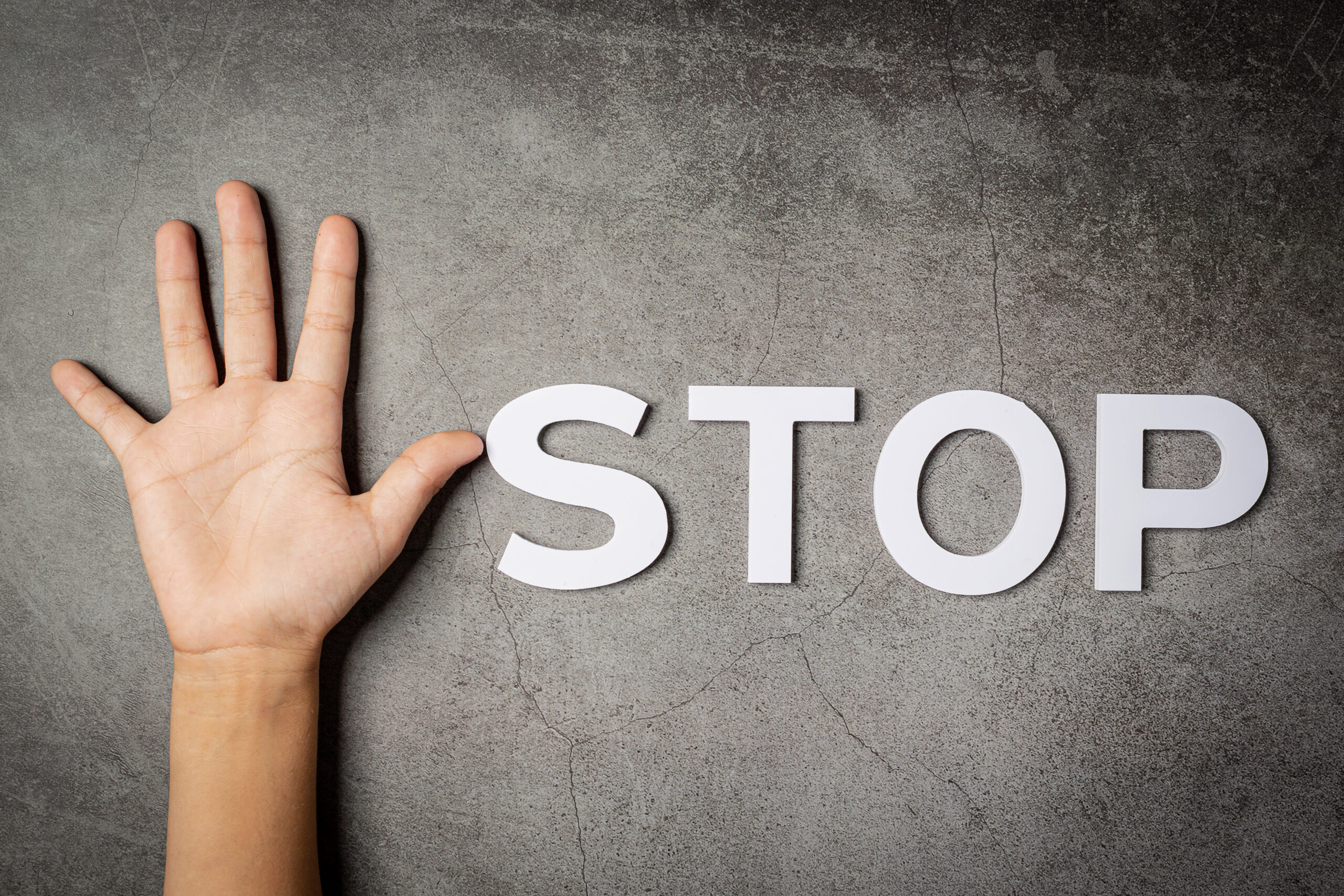 """word """"stop"""" with child's hand on dark background"""