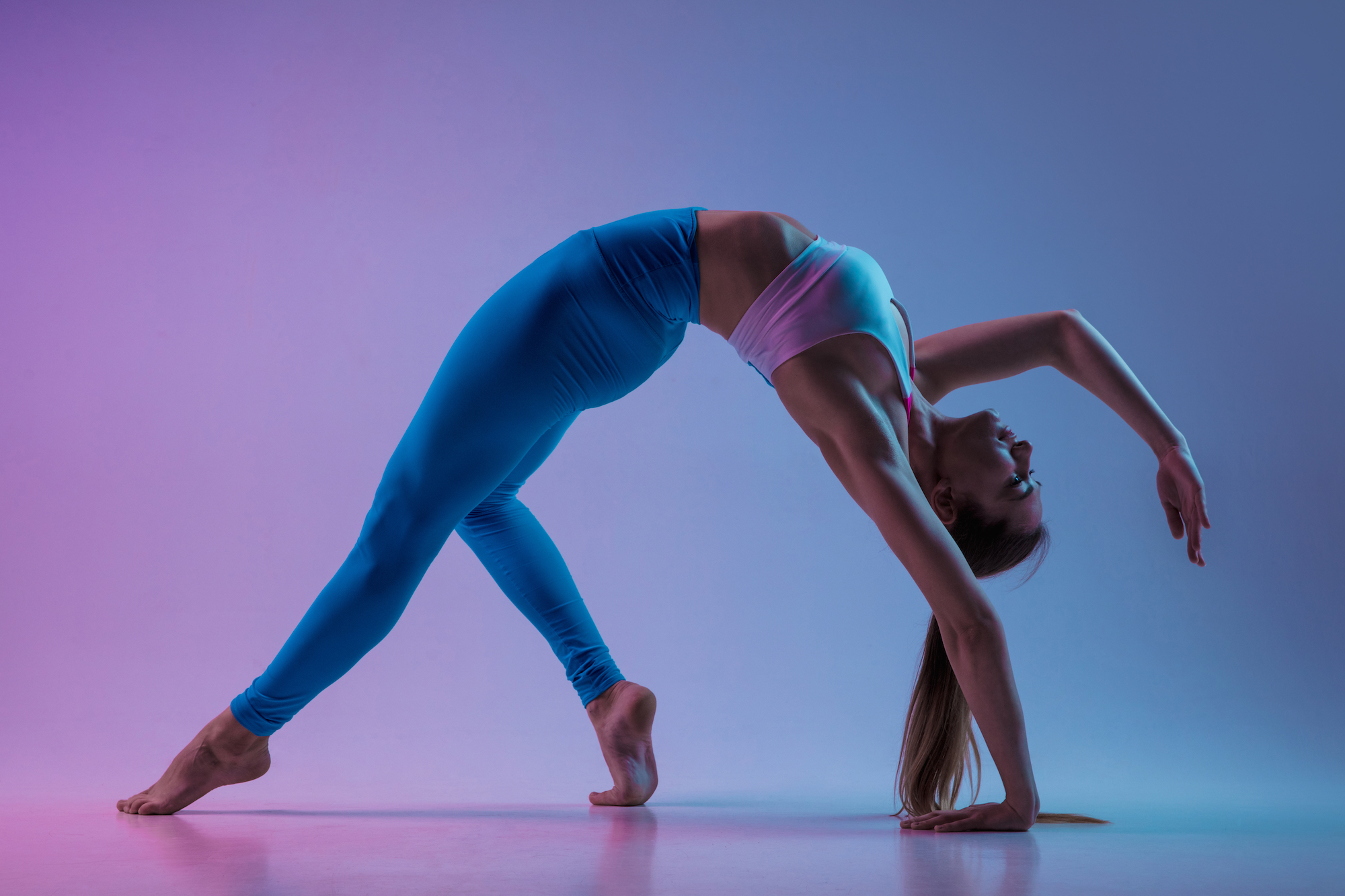 Young sportive woman training isolated on gradient studio background in neon light. athletic and graceful. Modern sport, action, motion, youth concept. Beautiful caucasian woman practicing.